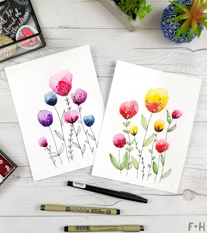 watercolor flower paintings on white desktop with art supplies