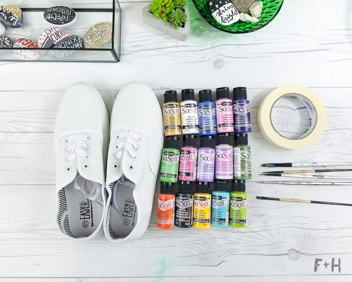 white canvas sneakers next to paint bottles
