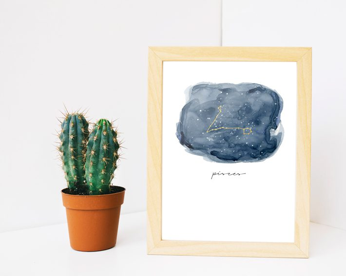 zodiac sign art in wood frame next to cactus on white background