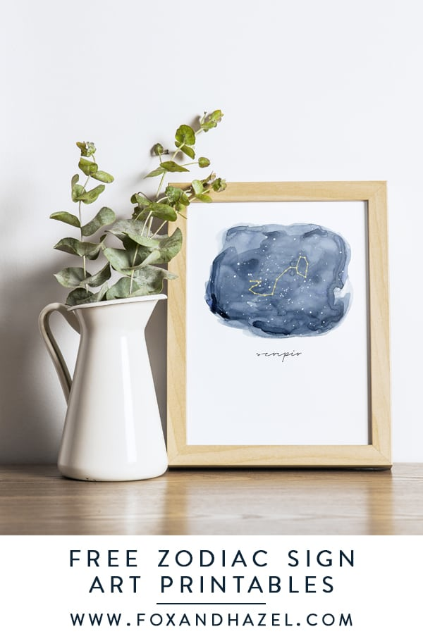 zodiac signs art in frame next to white vase with eucalyptus leaves