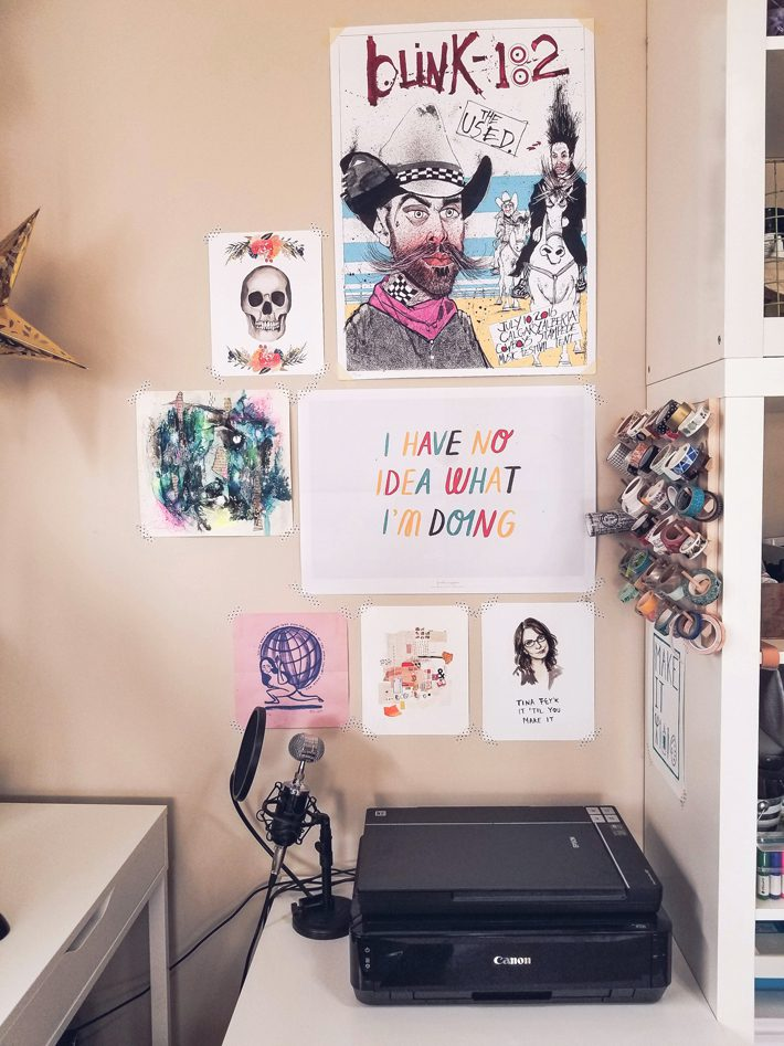 wall with art posters above printer