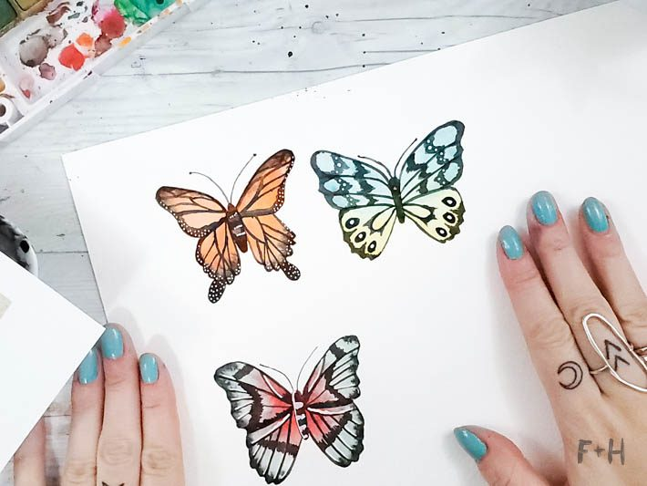 watercolor butterflies on white paper on desk